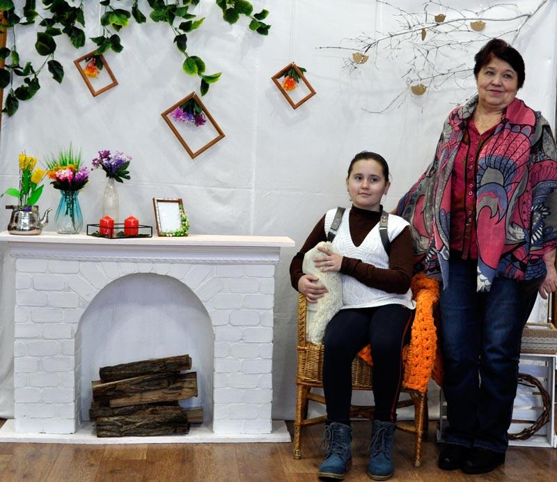 В фотоуголке на выставке В.Машенцевой находится Л.П. Гладких со своей внучкой